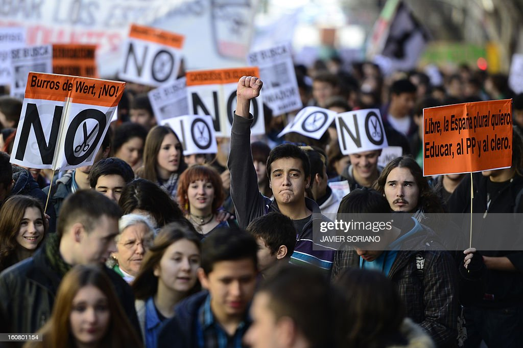 Spanish student gesture and brandish placards as they demonstrate against the law of Spanish Minister of Education, Culture and Sport Jose Ignacio Wert in Madrid on February 6, 2013.