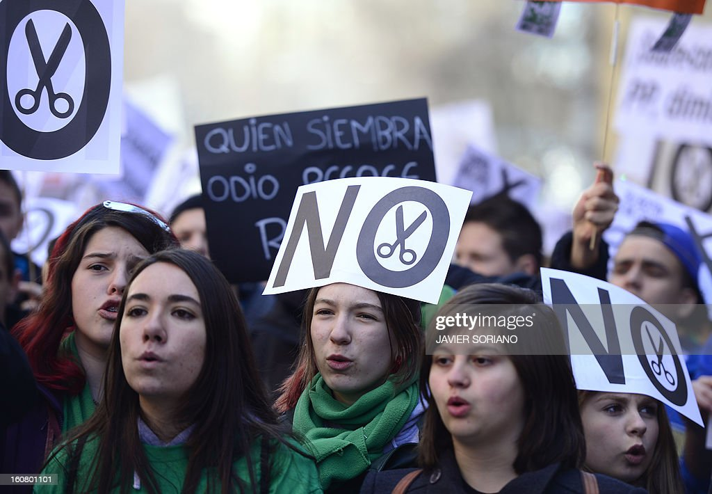 Spanish student hold placards as they demonstrate against the law of Spanish Minister of Education, Culture and Sport Jose Ignacio Wert in Madrid on February 6, 2013.