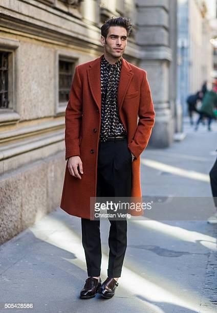 Spanish supermodel Jon Kortajarena wearing a dark orange peacoat printed tie and shirt and dark pleated trousers outside Salvatore Ferragamo during...