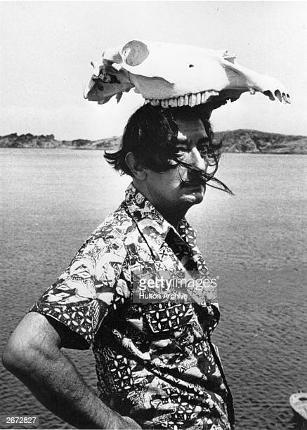 Spanish surrealist artist Salvador Dali wearing an animal skull as a hat