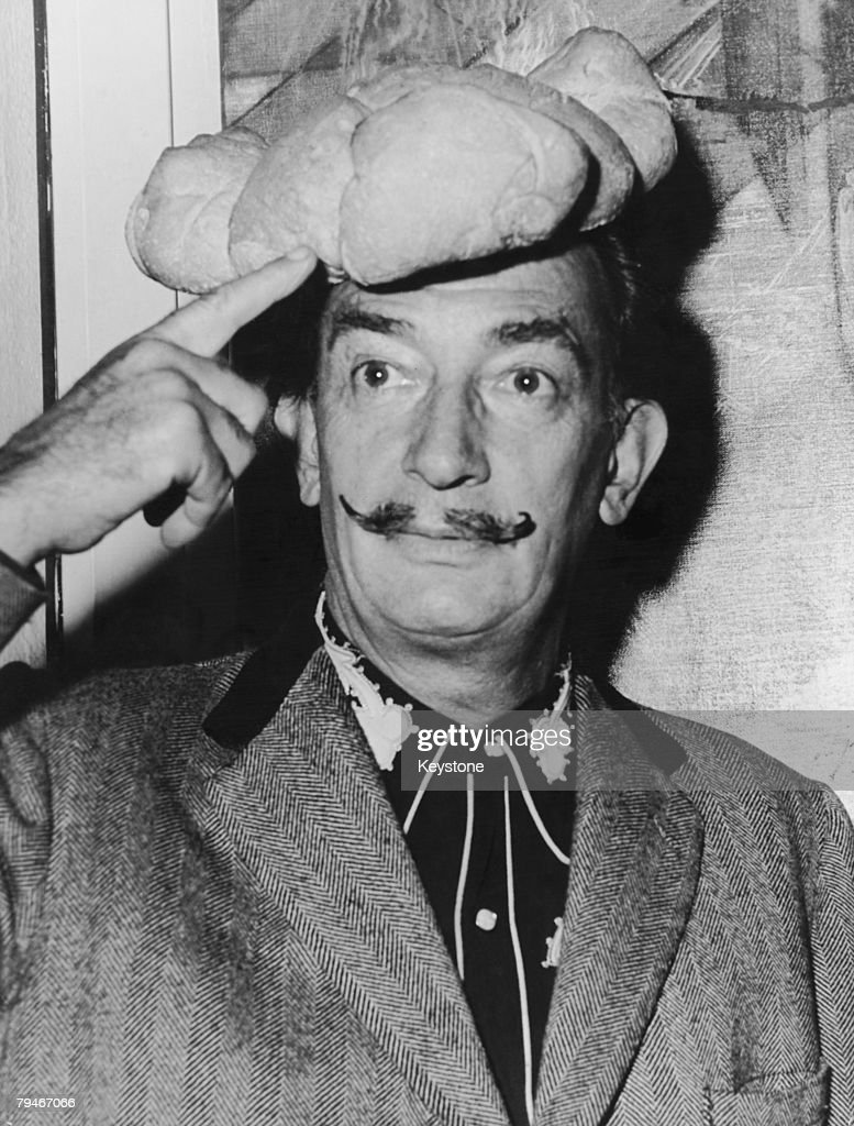 Spanish surrealist artist Salvador Dali wears a hat shaped like a loaf of bread on his head 5th November 1958