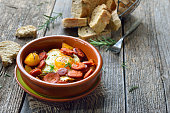 Spanish tapa: Spicy chorizo sausage with fried egg and baby potatoes served in a terra cotta cazuela dish