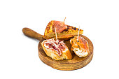 Typical spanish pub food pincho. Isolated on white background on a wooden board.