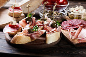 Spanish tapas with slices jamon serrano, salami, olives and cheese cubes on a wooden table. Spanish cuisine