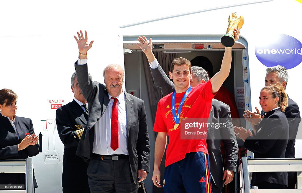 Spanish team captain Iker Casillas holds up the FIFA World Cup beside manager Vicente del Bosque at Barajas Airport on July 12, 2010 in Madrid, Spain.