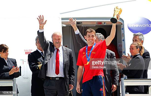 Spanish team captain Iker Casillas holds up the FIFA World Cup beside manager Vicente del Bosque at Barajas Airport on July 12 2010 in Madrid Spain