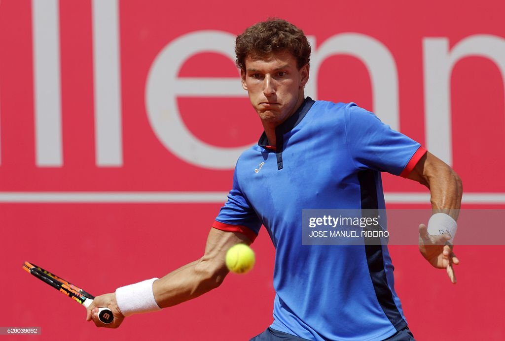 Spanish tennis player Pablo Carreno Busta returns a ball to French player Gilles Simon during their quarter-final match of the Estoril Open Tennis tournament in Estoril on April 29, 2016. / AFP / JOSE