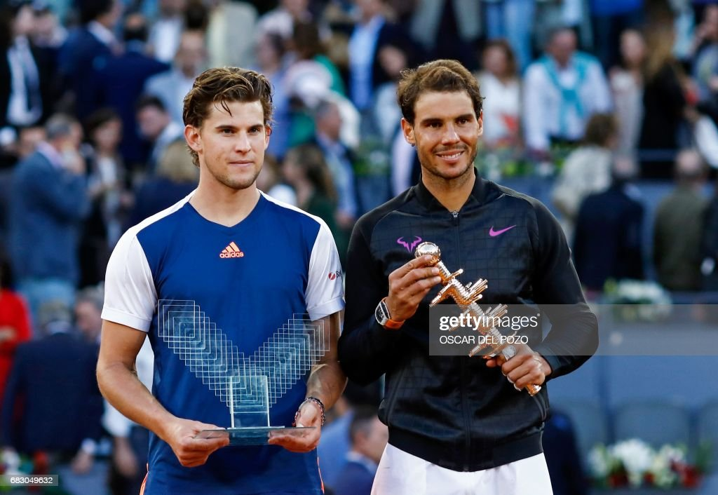 Spanish tennis player Rafael Nadal (R) and Austrian tennis player Dominic Thiem pose with their trophies at the end of their ATP Madrid Open final match in Madrid, on May 14, 2017. Nadal won 7-6 and 6-4. /