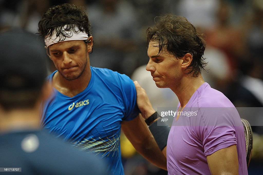 Spanish tennis player Rafael Nadal (R) greets Brazilian Joao Souza after defeating him in a Brazil Open single match at Ibirapuera gymnasium in Sao Paulo, Brazil, on February 14, 2013. Nadal withdrew his doubles match yesterday because of his left knee concern. AFP PHOTO/Yasuyoshi CHIBA