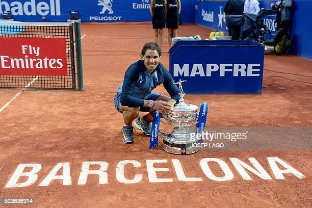 Spanish tennis player Rafael Nadal poses with his trophy as he celebrates his victory over Japanese tennis player Kei Nishikori after the final of...