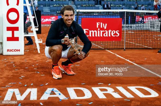 Spanish tennis player Rafael Nadal poses with his trophy as he celebrates his victory over Austrian tennis player Dominic Thiem at the end of their...