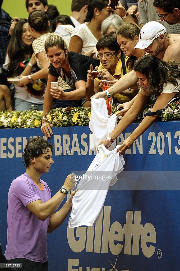 Spanish tennis player Rafael Nadal signs autographs to fans at the end of his Brazil Open single match against Brazilian Joao Souza, at Ibirapuera gymnasium in Sao Paulo, Brazil, on February 14, 2013. Nadal withdrew his doubles match yesterday because of his left knee concern. AFP PHOTO/Yasuyoshi CHIBA