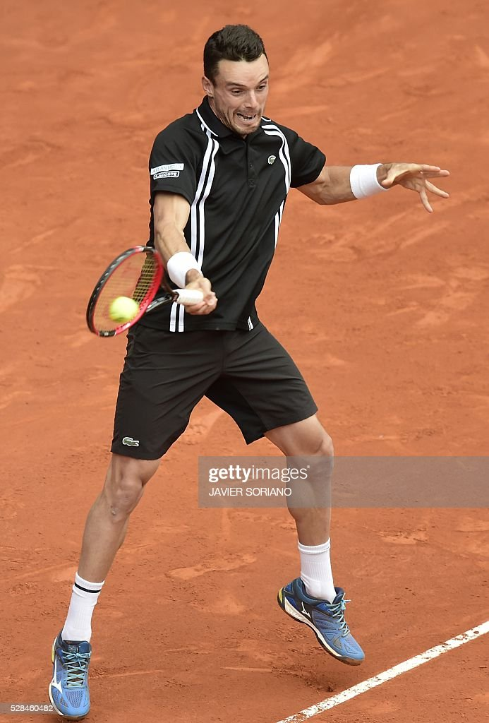 Spanish tennis player Roberto Bautista returns a ball to Serbian tennis player Novak Djokovic during the Madrid Open tournament at the Caja Magica (Magic Box) sports complex in Madrid on May 5, 2016. / AFP / JAVIER
