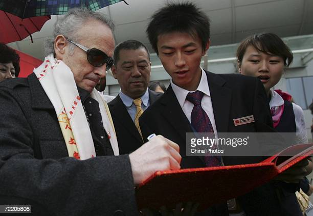 Spanish tenor Jose Carreras signs an autograph for organizers of '2006 Pageant Xian' on arrival at Xian Xianyang International Airport October 18...