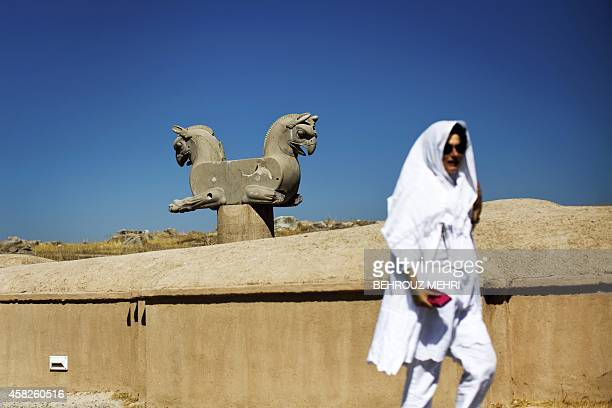 Spanish tourist walks past an Achaemenid griffin at the ancient Persian city of Persepolis near Shiraz in southern Iran on September 26 2014 At the...