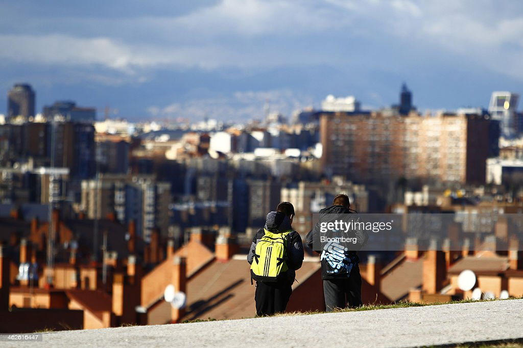 Spanish youths walk along a street with a view across the city skyline and the rooftops of residential housing in Madrid, Spain, on Monday, Jan. 13, 2014. Spain's rental market is growing as government-spending cuts, a 26 percent jobless rate and subdued mortgage lending make home buying more difficult. Photographer: Angel Navarrete/Bloomberg via Getty Images