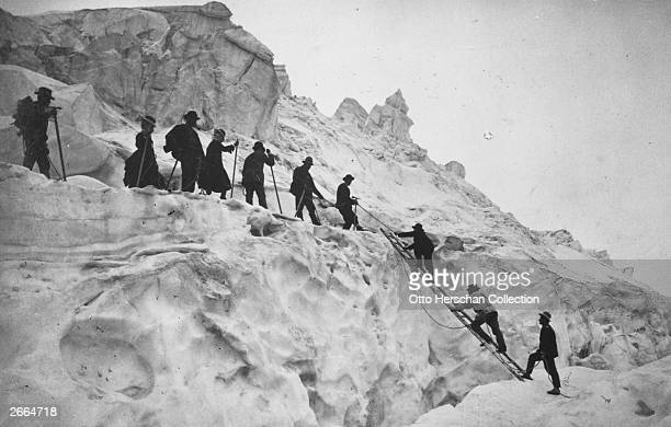 Spanning a crevasse with the help of a ladder a mixed group go mountaineering in the Alps