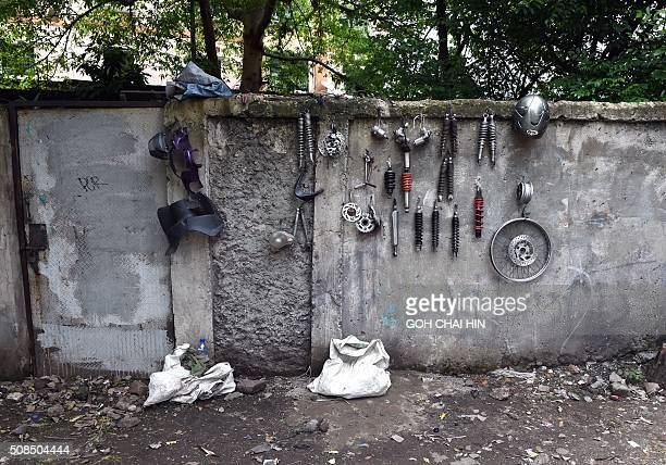 Spare parts for motorbikes hang from a wall at a makeshift repair shop along a street in Jakarta on February 5 2016 Indonesia's economy grew at its...