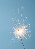 Close up of a burning sparkler on a blue background