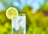Sparkling water and lemon slice on glass with an ice, sunny day - narrow focus on middle of the glass