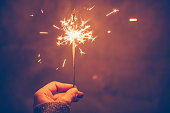 Close up of woman's hand holding sparklers on dark bakground.