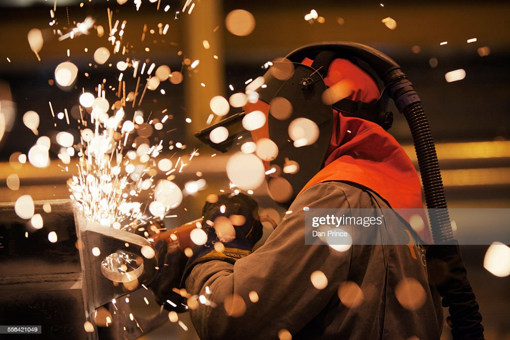 Sparks and worker using grinder