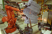 Orange industrial welding robot in a car manufacturing plant. The robot just grabbed car part and starts welding while sparks are flying around.