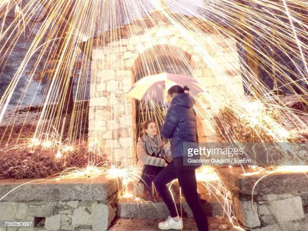 Sparks Falling On Woman Holding Umbrella By Friend Sitting On Steps