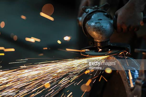 Sparks fly as an employee uses an angle grinder inside an Ishwar Engineering Co factory in Mumbai Maharashtra India on Saturday Feb 7 2015 The...