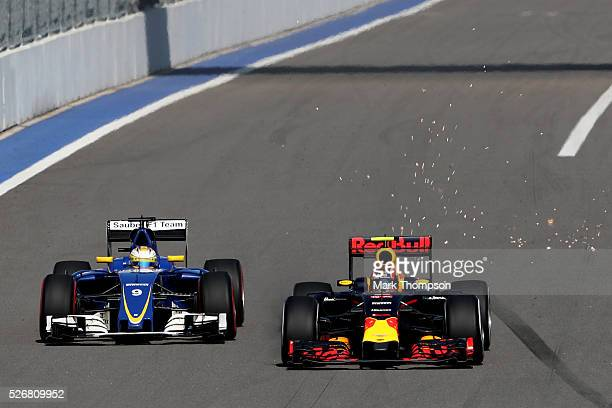 Sparks fly as Daniil Kvyat of Russia driving the Red Bull Racing Red BullTAG Heuer RB12 TAG Heuer battles for position on track with Marcus Ericsson...