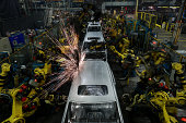 Sparks fly as robots weld the frames of Honda Motor Co Odyssey minivans on the assembly line at Honda Manufacturing of Alabama LLC facility in...