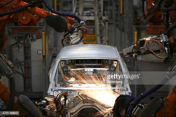 Sparks fly as robots weld together a Bayerische Motoren Werke AG X4 sports utility vehicle body frame at the BMW Manufacturing Co assembly plant in...