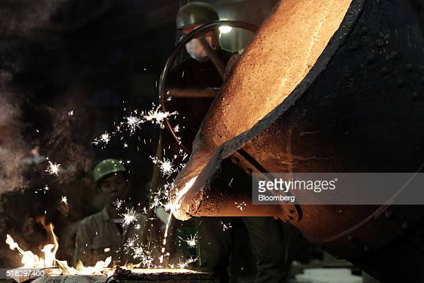 Sparks fly as workers monitor and pour molten metal from a ladle into a casting mold at the Tomiwa Chuzo Co foundry in Kawaguchi Saitama Prefecture...