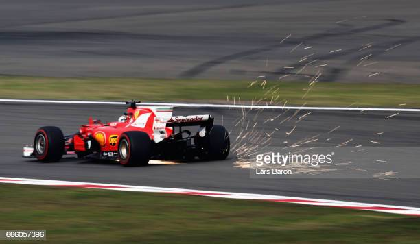 Sparks fly behind Sebastian Vettel of Germany driving the Scuderia Ferrari SF70H on track during qualifying for the Formula One Grand Prix of China...