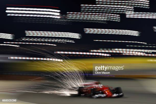 Sparks fly behind Sebastian Vettel of Germany driving the Scuderia Ferrari SF70H on track during practice for the Bahrain Formula One Grand Prix at...