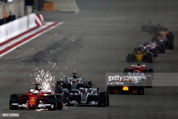 Sparks fly behind Sebastian Vettel of Germany driving the Scuderia Ferrari SF70H ahead of Valtteri Bottas driving the Mercedes AMG Petronas F1 Team...