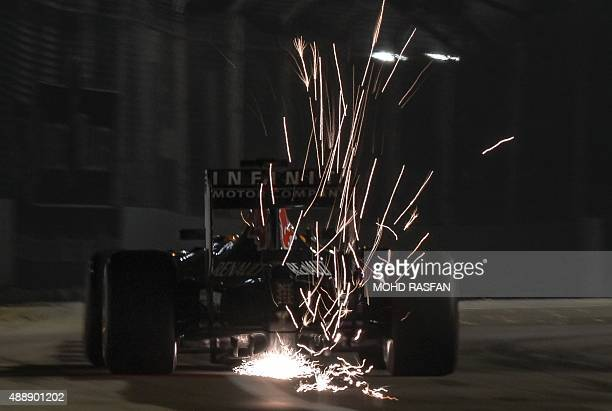 Sparks fly behind the car of Infiniti Red Bull Racing's Australian driver Daniel Ricciardo during the second free practice session ahead of the...