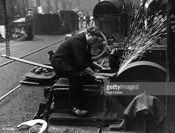 Sparks flying as a workman polishes cylinder covers for a streamline engine at a locomotive works Original Publication Picture Post 393 Making Of A...