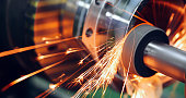 sparks flying while machine griding and finishing metal in factory