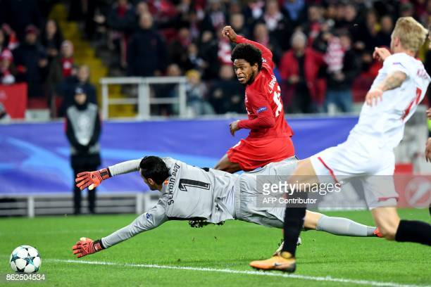 TOPSHOT Spartak Moscow's forward from Brazil Luiz Adriano scores the team's fourth goal past Sevilla's goalkeeper from Spain Sergio Rico Gonzalez...