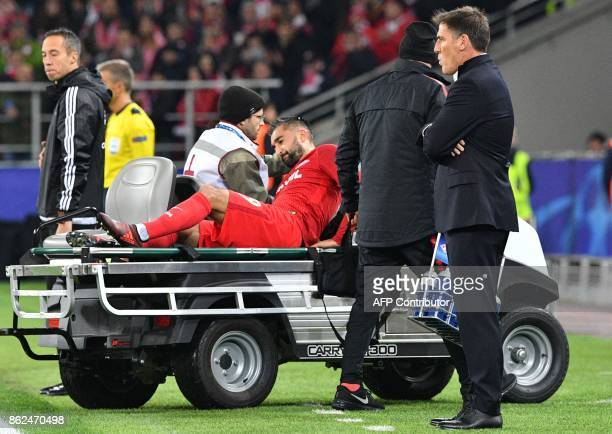 Spartak Moscow's midfielder from Russia Alexander Samedov is transported off the field as Sevilla's coach from Argentina Eduardo Berizzo stands...