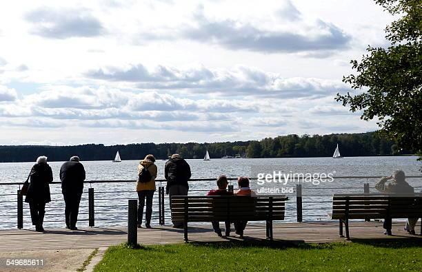 Spaziergänger auf einer Bank im Kurpark am Ufer vom Scharmützelsee in Bad Saarow