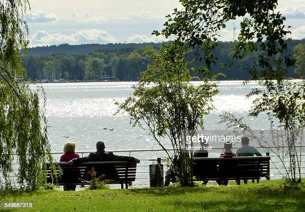 Spaziergänger sitzen am Ufer des Scharmützelsee in Bad Saarow