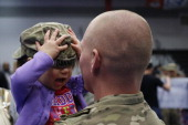 Spc Brian Bennett of the US Army's 3rd Brigade Combat Team 1st Infantry Division holds his 2yearold daughter Sophia following a homecoming ceremony...