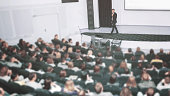Speaker at a business convention and presentations. The audience on the large number of people. The announcer with a microphone in his hands