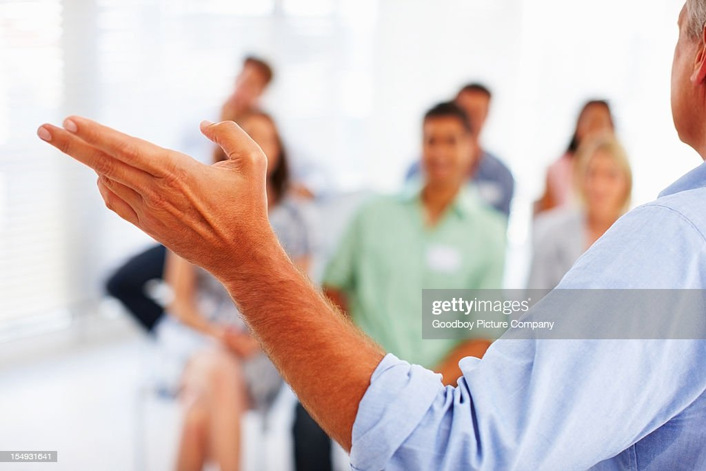 Speaker giving presentation to business people : Stock Photo