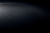 Black metal speaker grille with very shallow depth of field.