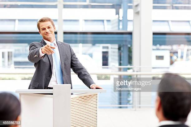 Speaker in suit pointing to audience member
