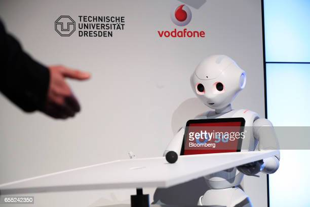 A speaker interacts with a 5G connected 'Pepper' humanoid robot manufactured by SoftBank Group Corp during a Vodafone GmbH news conference at the...