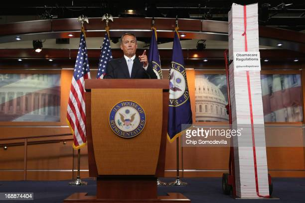 Speaker of the House John Boehner stands next to a printed version of the Patient Protection and Affordable Care Act or Obamacare during a news...